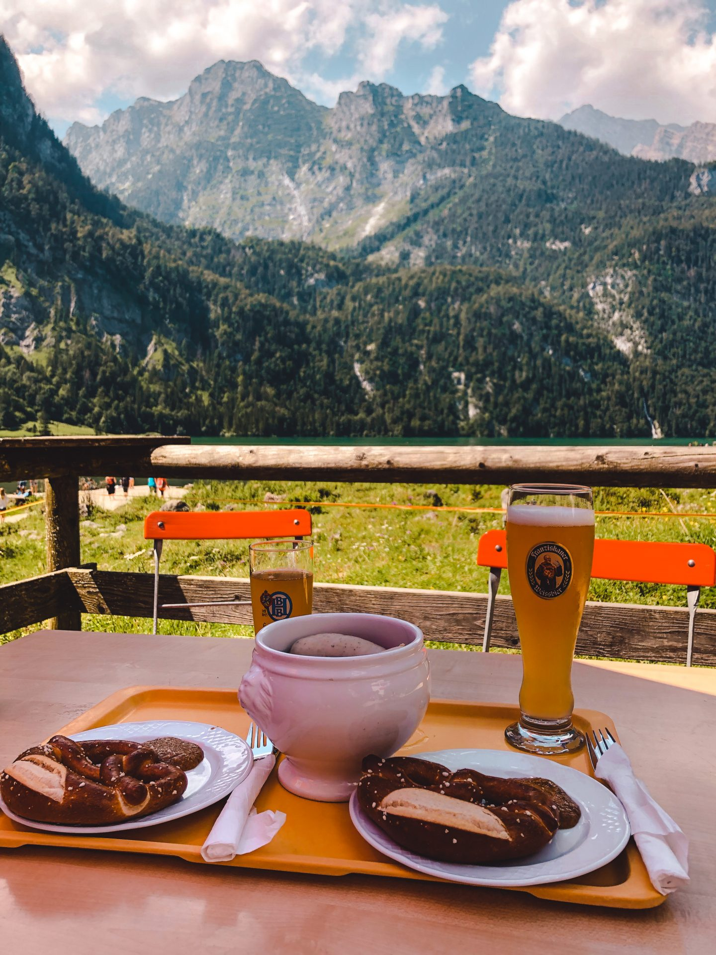 A traditional Bavarian breakfast containing white sausages and white beer and a pretzel